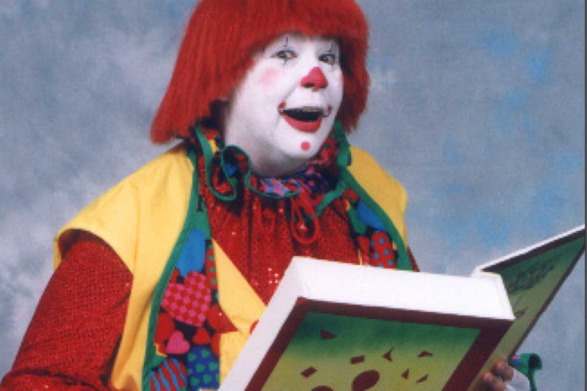 Clown reading from a large book
